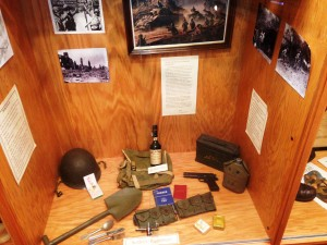 116th Infantry Regiment World War II Equipment, Canteen, us Cal ,45 Automatic pistol, cartridge Belt, Entrenching Tool (shovel), Pack, helmet, eating utensils, C-Ration Cigarettes, Calvados Wine, and Ammo Box