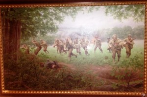 "The ""Major of St. Lo"", Major Thomas D. Howie Commemorative Painting shows the 3rd 116th Infantry Battalion starting the attack on St. Lo, as Howie is fatally wounded by enemy Mortar fire accurately captured by this painting."
